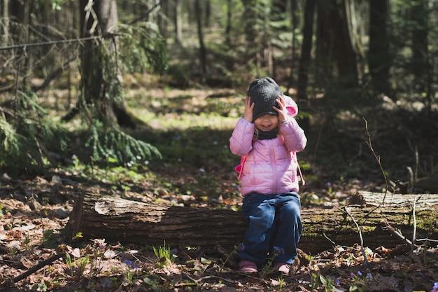 Śliczna mała dziewczynka siedzi na logu lesie