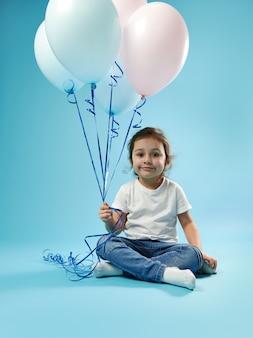 Śliczna mała dziewczynka siedzi na niebieskiej powierzchni z miękkim cieniem i pozuje do przodu z balonami w dłoni