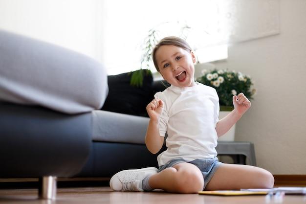 Śliczna mała dziewczynka siedzi na podłodze w domu, grając, rysując, czując się figlarnie i dobrze się bawiąc