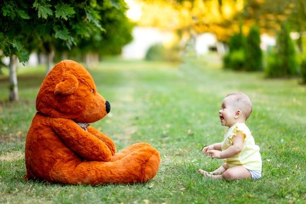 Śliczna mała dziewczynka siedzi na trawie z wielkim misiem