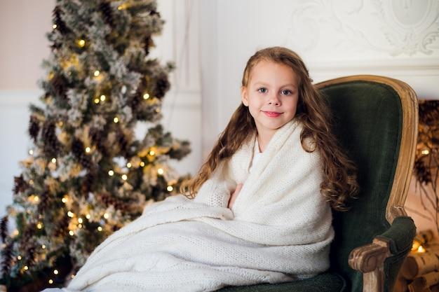 Śliczna mała dziewczynka siedzi przy choince owinięta w ciepły koc w domu