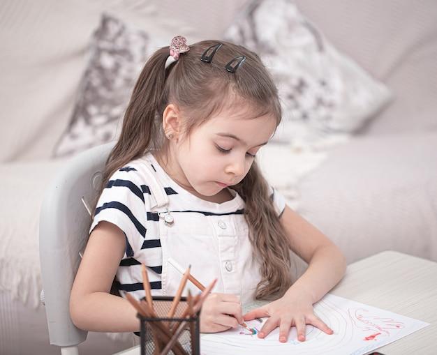 Śliczna mała dziewczynka siedzi przy stole i odrabia lekcje. edukacja domowa i edukacja