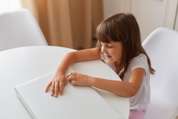 Śliczna mała dziewczynka siedzi przy stole z białym zamkniętym laptopem, ciemnowłose dziecko płci żeńskiej pozuje w jasnym pokoju w stylu casual, zamykając, kryty strzał.
