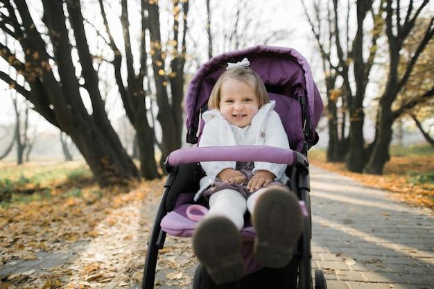 Śliczna mała dziewczynka siedzi w fioletowy wózek dziecięcy