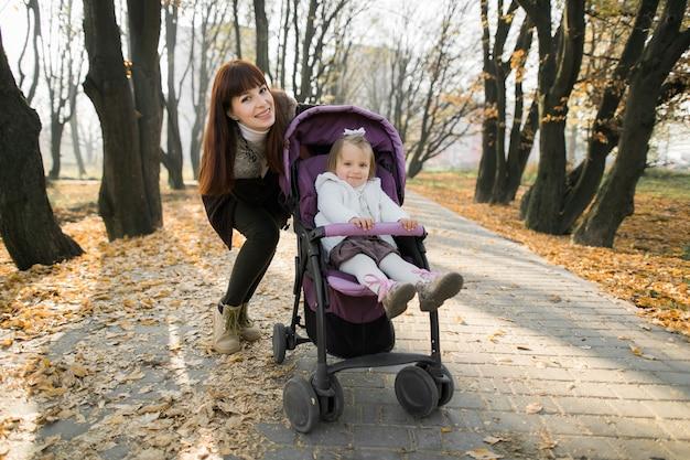 Śliczna mała dziewczynka siedzi w fioletowym wózku obok matki