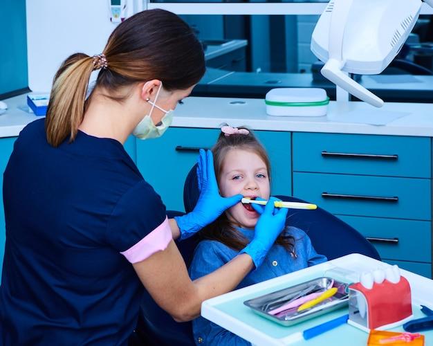 Śliczna mała dziewczynka siedzi w gabinecie dentystów