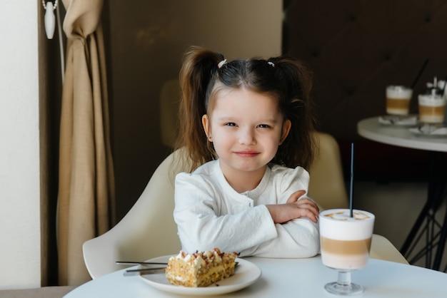 Śliczna mała dziewczynka siedzi w kawiarni i patrzeje zbliżenie ciasto i kakao. dieta i prawidłowe odżywianie.