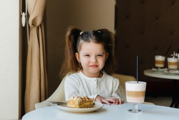 Śliczna mała dziewczynka siedzi w kawiarni i patrzy na ciasto i kakao