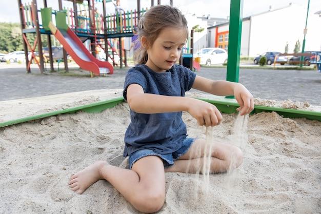 Śliczna mała dziewczynka siedzi w piaskownicy i bawi się piaskiem w upalny letni dzień.