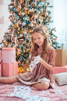Śliczna mała dziewczynka siedzi w pobliżu drzewa i robi papierowe płatki śniegu
