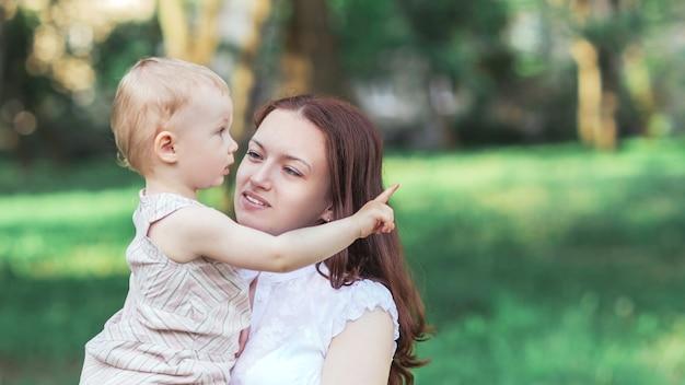 Śliczna mała dziewczynka siedzi w ramionach swojej mamy. zdjęcie z miejscem na kopię