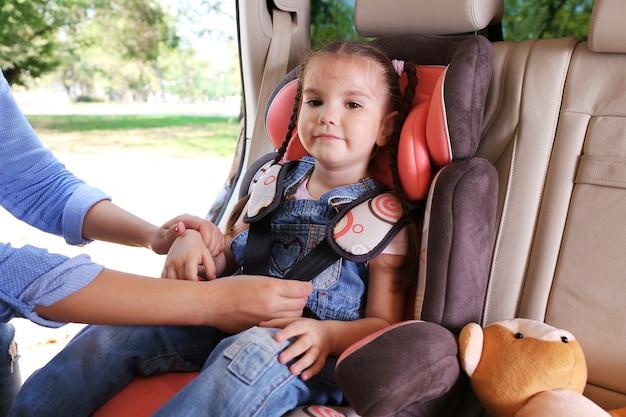 Śliczna mała dziewczynka siedzi w samochodzie