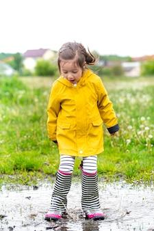Śliczna mała dziewczynka skacze do kałuży. beztroskie dzieciństwo