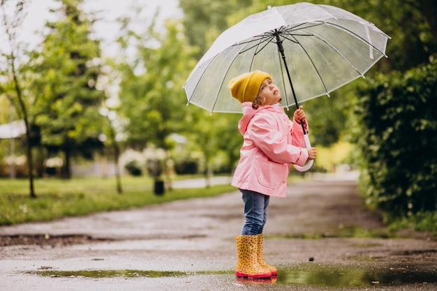 Śliczna mała dziewczynka skacze w kałużę w dżdżystej pogodzie