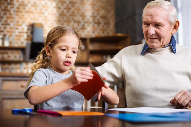 Śliczna mała dziewczynka składając papier robiąc świąteczną kartkę ze swoim dziadkiem
