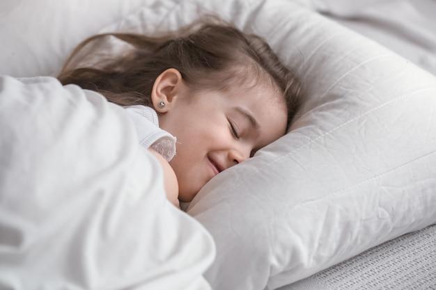 Śliczna mała dziewczynka słodko śpi w łóżku