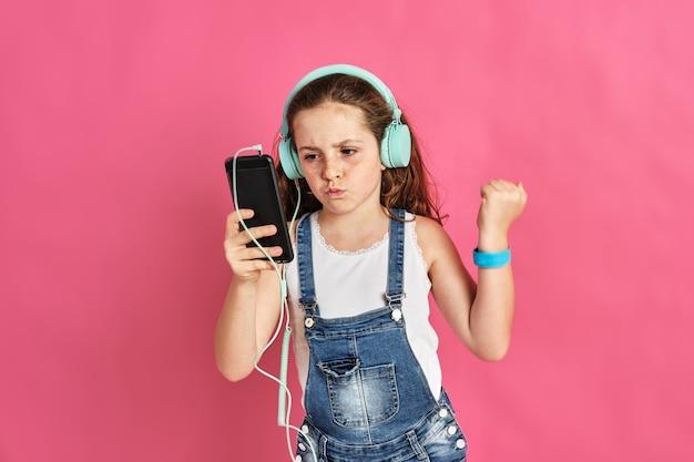 Śliczna mała dziewczynka słucha muzyki przez telefon i słuchawki