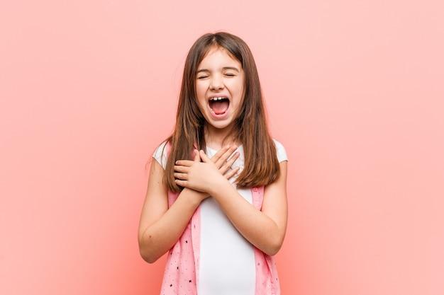 Śliczna mała dziewczynka śmia się utrzymujący ręki na sercu, szczęście.