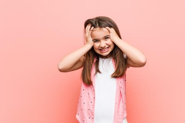 Śliczna mała dziewczynka śmieje się z radością trzymając ręce na głowie. koncepcja szczęścia.
