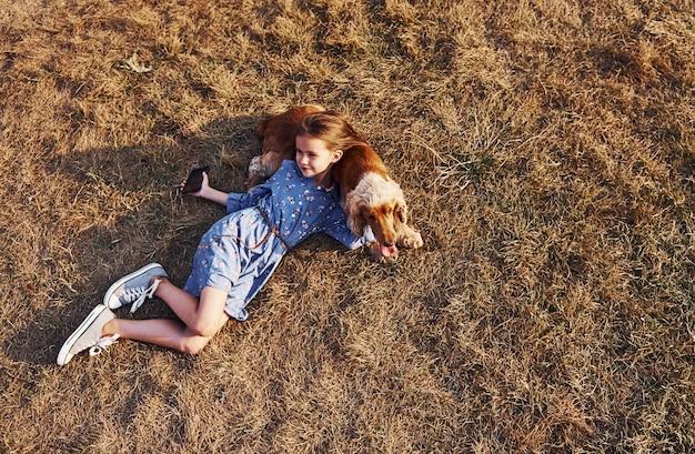 Śliczna mała dziewczynka spaceruje z psem na zewnątrz w słoneczny dzień