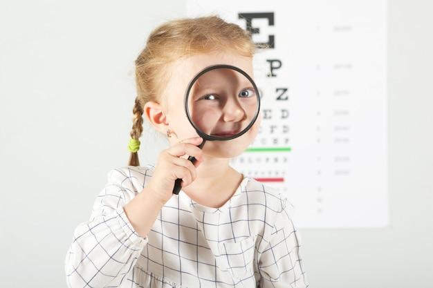 Śliczna mała dziewczynka sprawdza wzrok za pomocą testu wzroku okulisty