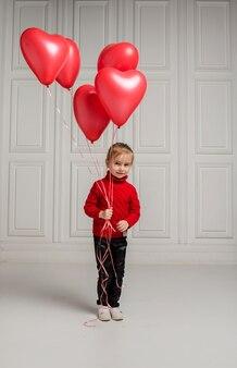 Śliczna mała dziewczynka stoi i trzyma z czerwonymi balonami w kształcie serca na białym tle
