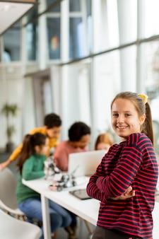 Śliczna Mała Dziewczynka Stoi Przed Grupą Dzieci Programujących Zabawki Elektryczne I Roboty W Klasie Robotyki Premium Zdjęcia