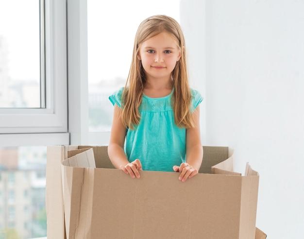 Śliczna mała dziewczynka stoi w dużym pudełku tekturowym, chcąc bawić się w hideandseek
