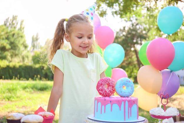 Śliczna mała dziewczynka świętuje urodziny na zewnątrz