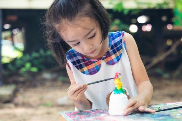 Śliczna mała dziewczynka szczęśliwie uczy się poza klasą z piękną naturą i promiennym uśmiechem