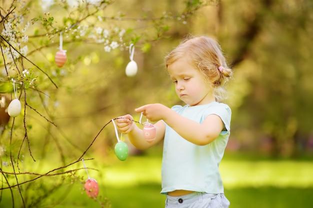 Śliczna mała dziewczynka tropi dla easter jajka na gałęziastym kwiatonośnym drzewie.