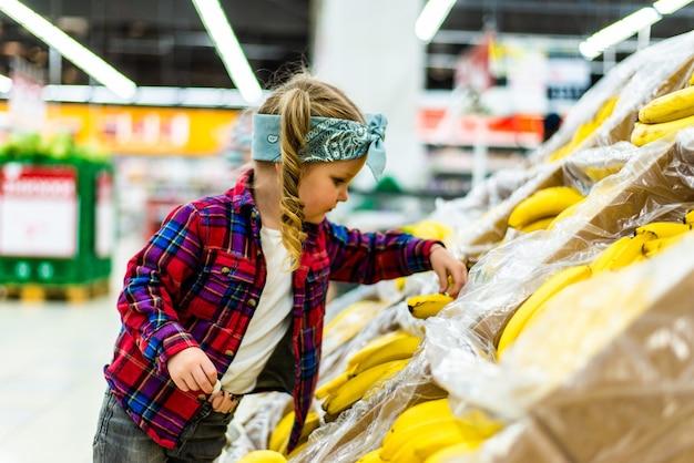Śliczna mała dziewczynka trzyma banany w sklepie spożywczym lub supermarkecie