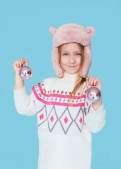 Śliczna mała dziewczynka trzyma boże narodzenie kule ziemskie