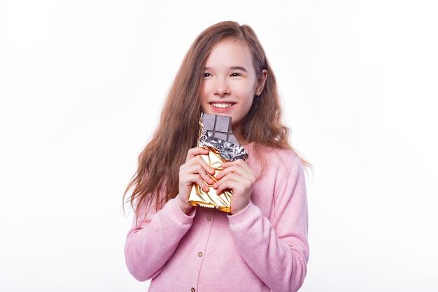 Śliczna mała dziewczynka trzyma czekoladę na białej ścianie
