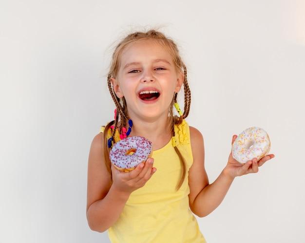 Śliczna mała dziewczynka trzyma dwa pączka