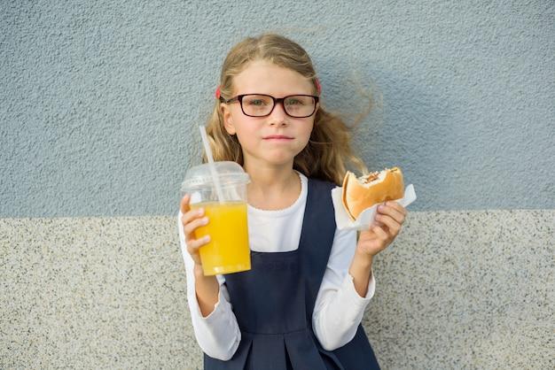 Śliczna mała dziewczynka trzyma hamburgeru sok pomarańczowego