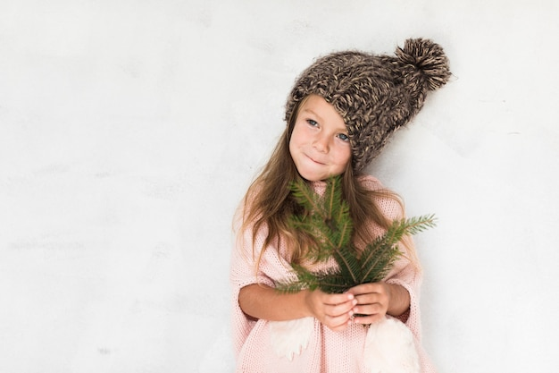 Śliczna mała dziewczynka trzyma jodły gałąź