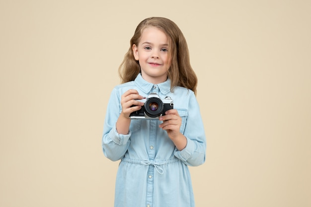 Śliczna mała dziewczynka trzyma kamerę