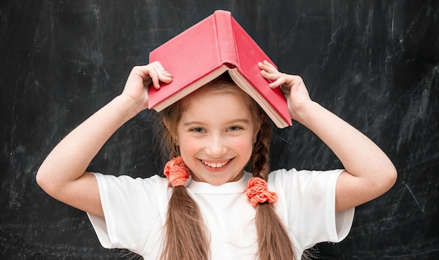 Śliczna mała dziewczynka trzyma książkę na głowie