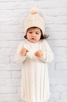 Śliczna mała dziewczynka trzyma płatek śniegu