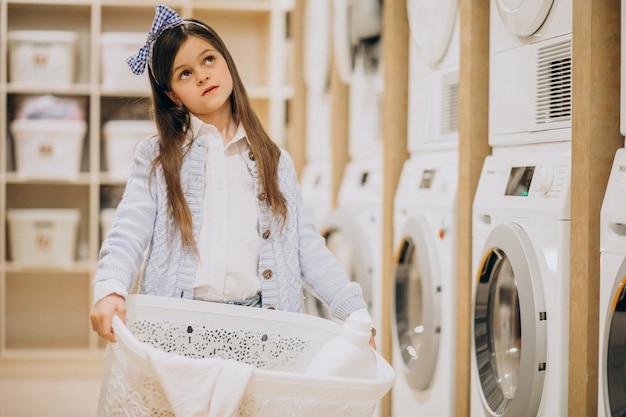 Śliczna mała dziewczynka trzyma pralnianego kosz