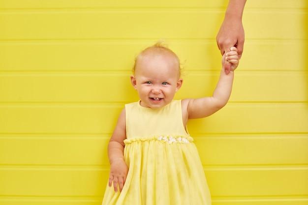 Śliczna mała dziewczynka trzyma rękę dorosłego i uśmiecha się na żółtym tle.