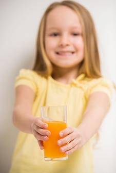 Śliczna mała dziewczynka trzyma szkło sok