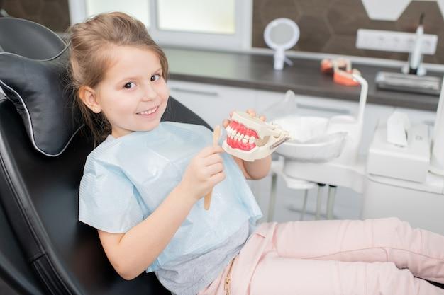 Śliczna mała dziewczynka trzyma sztuczne zęby i szczoteczkę do zębów siedząc w skórzanym fotelu przed kamerą we współczesnych klinikach stomatologicznych