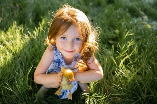 Śliczna mała dziewczynka trzyma w rękach kaczątko
