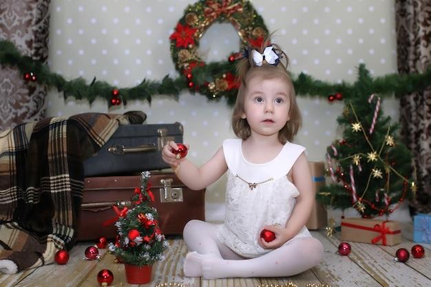 Śliczna mała dziewczynka ubiera choinkę na podłodze w pokoju