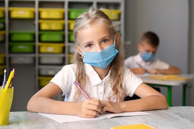 Śliczna mała dziewczynka ubrana w maskę medyczną