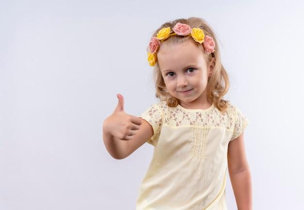 Śliczna mała dziewczynka ubrana w żółtą koszulkę w kwiecistej opasce pokazująca kciuki do góry, patrząc na białą ścianę