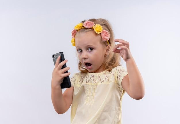 Śliczna mała dziewczynka ubrana w żółtą koszulkę w kwiecistej opasce zaskakująca, trzymając telefon komórkowy na białej ścianie