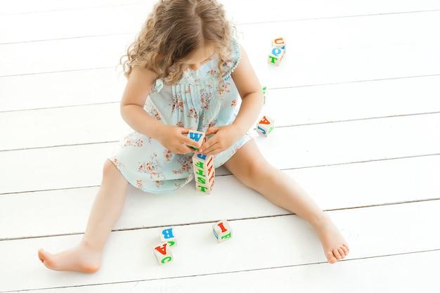 Śliczna mała dziewczynka uczy się czytać. urocze dziecko kształci. dziecko bawiąc się kostkami abc